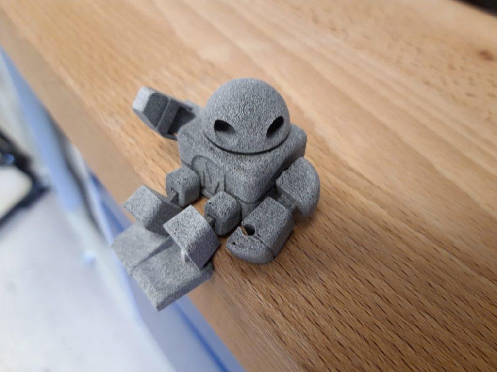 grauer winkender Robotter aus dem 3D-Druck