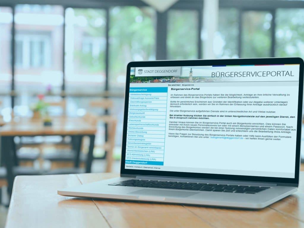 Die Website des Bürgerserviceportals geöffnet in einem Browser auf einem Laptop. Im Hintergrund ist das Ambiente eines Cafes zu erkennen.