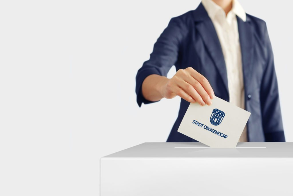 Frau mit Wahlumschlag der STadt Deggendorf beim Einwerfen in eine Wahlurne