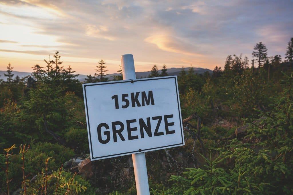 """Weißes Schild im Waldgebiet mit der Aufschrift """"15km Grenze"""""""