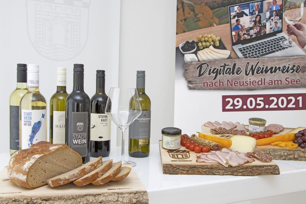 Mehrere Flaschen Weißwein und Rotwein auf einem gedeckten Tisch mit regionaler Brotzeit der Digitalen Weinverkostung der Stadt Deggendorf