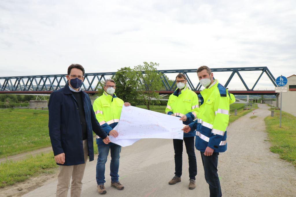 OB Christian Moser mit Mitarbeiter des Wasserwirtschaftsamt Deggendorf mit einem Plan der Umbaumaßnahmen des Hochwasserschutzes in Natternberg