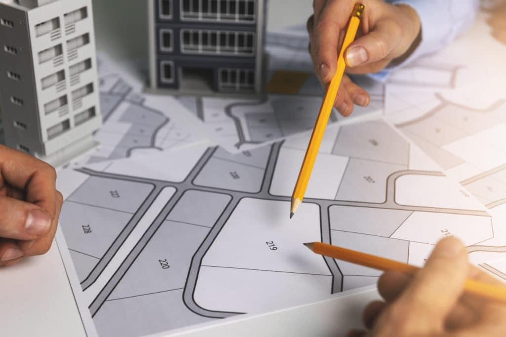 Stadtplan und Modellhäuser mit mehreren Menschen, die darüber diskutieren