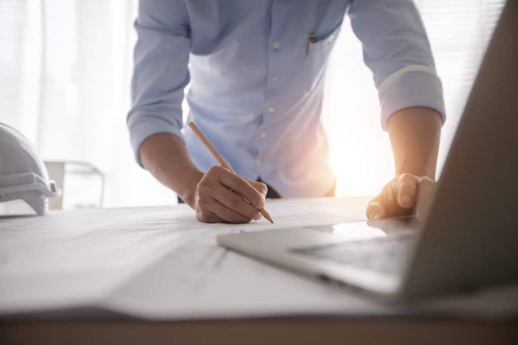 Mann steht hinter seinem Schreibtisch und entwirft einen Plan