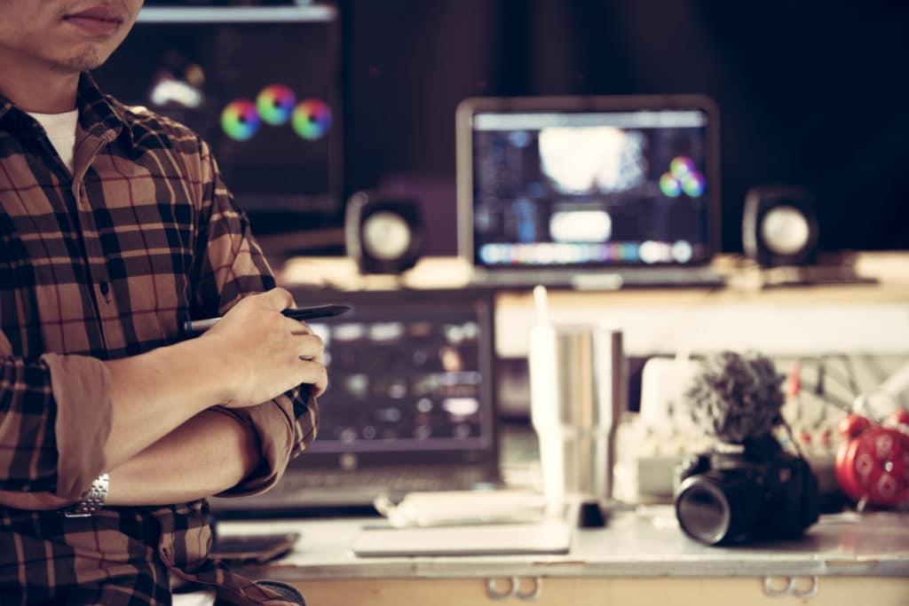 Online-Redakteur in einem Büro mit mehreren PCs und Foto-Kameras