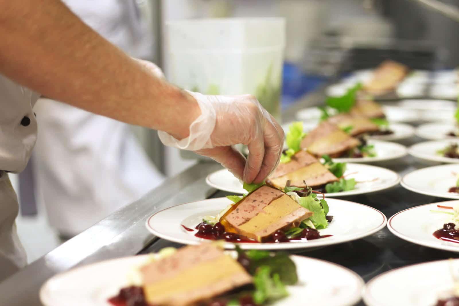 Koch platziert Salat zum Dessert auf einen Teller in einer Großküche