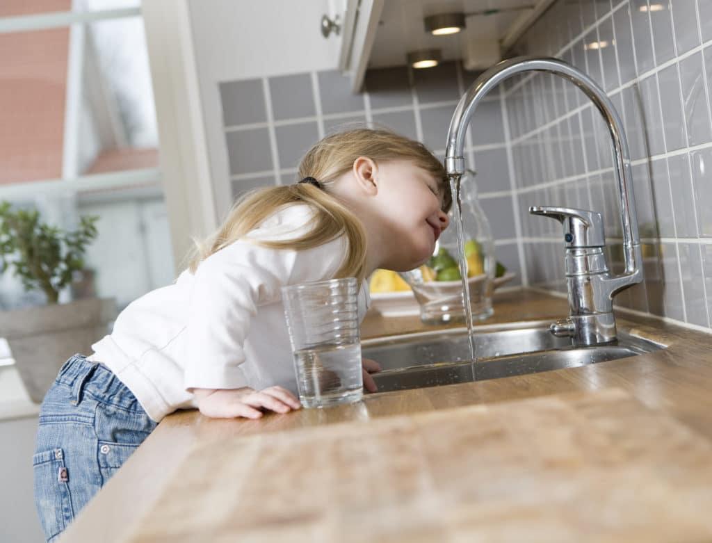 Kleines Mädchen trinkt Leitungswasser auf dem Wasserhahn in der Küche