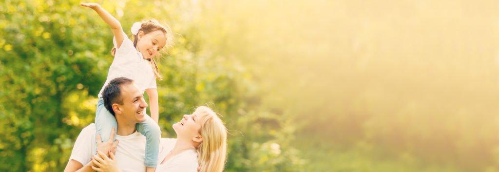 Mutter & Vater mit Kind auf dem Rücken im Park