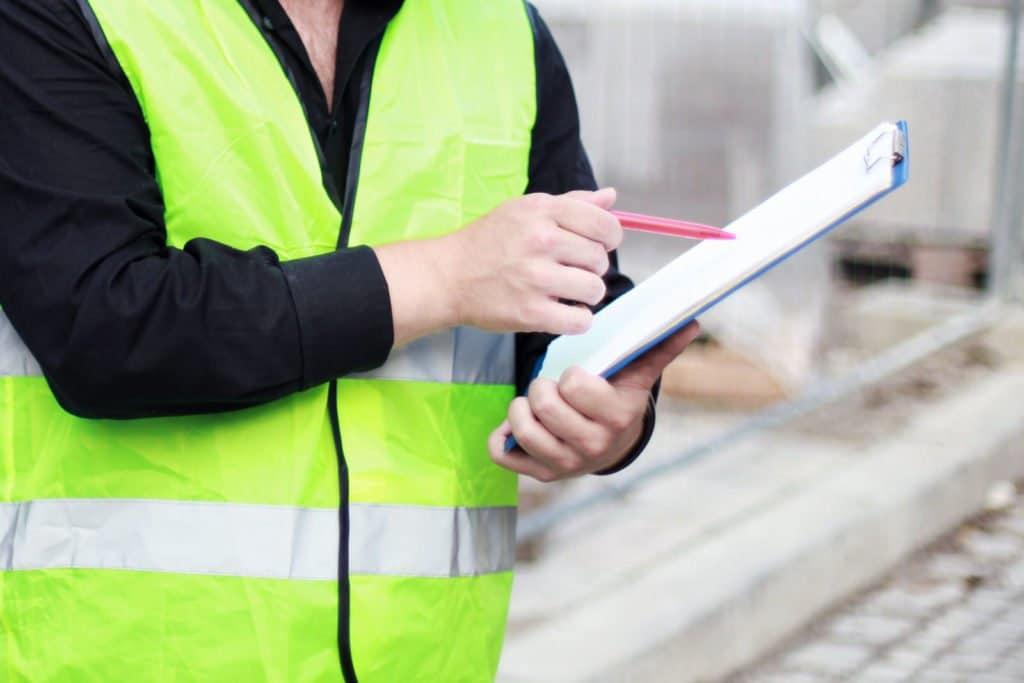 Bauleiter mit Warnweste und Schreibbrett auf der Baustelle