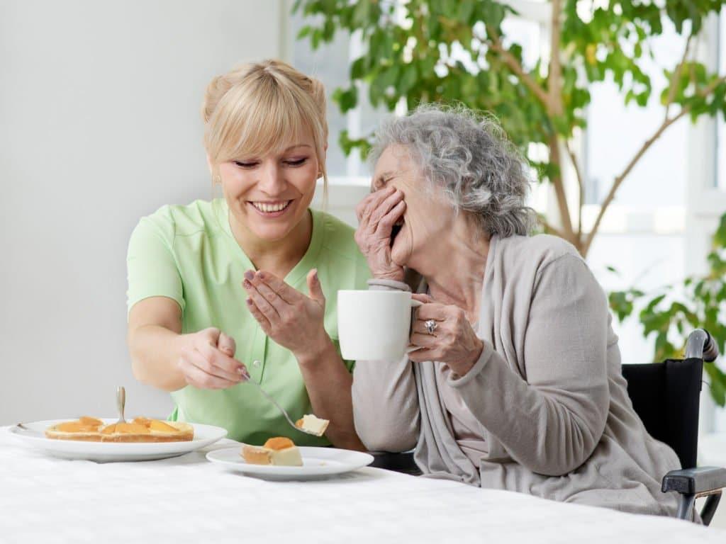 Pflegekraft unterhält sich mit einer älteren Dame während des Kaffeetrinkens am gedeckten Tisch