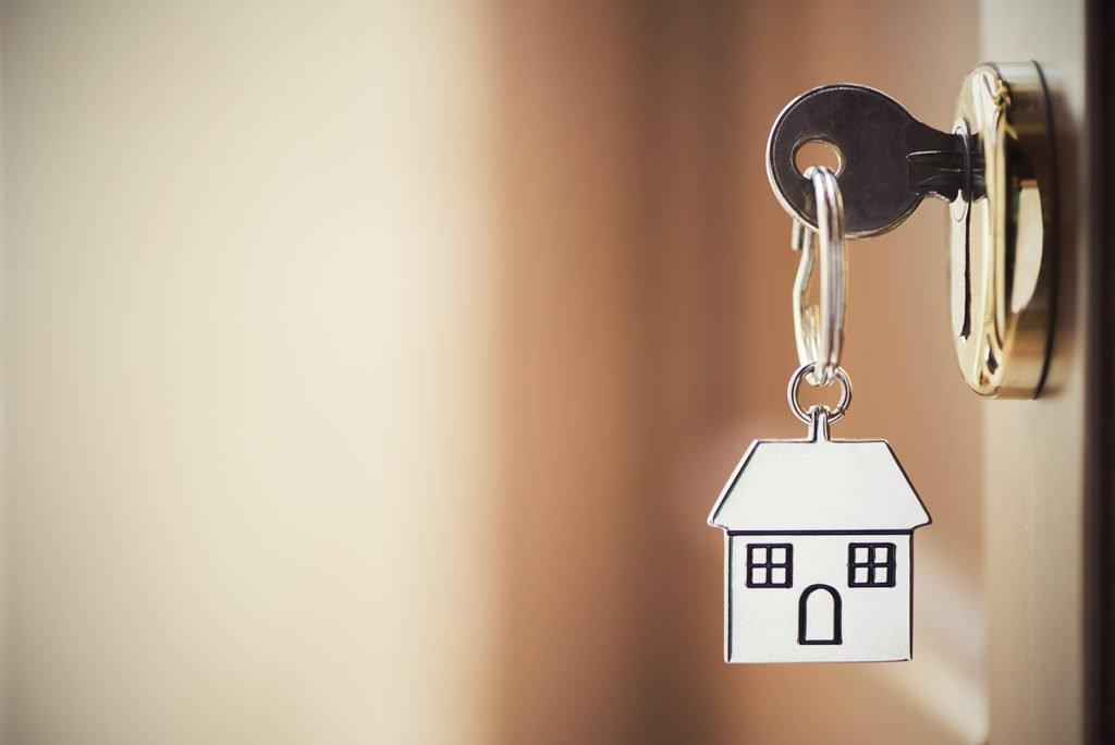 Ein Schlüssel mit einem Haus-Anhänger steckt in einem Türschloss in einer Wohnungstür