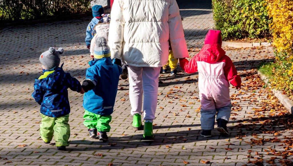 Kindergartenkinder an der Hand einer Erzieherin unterwegs auf einem gepflasterten Weg