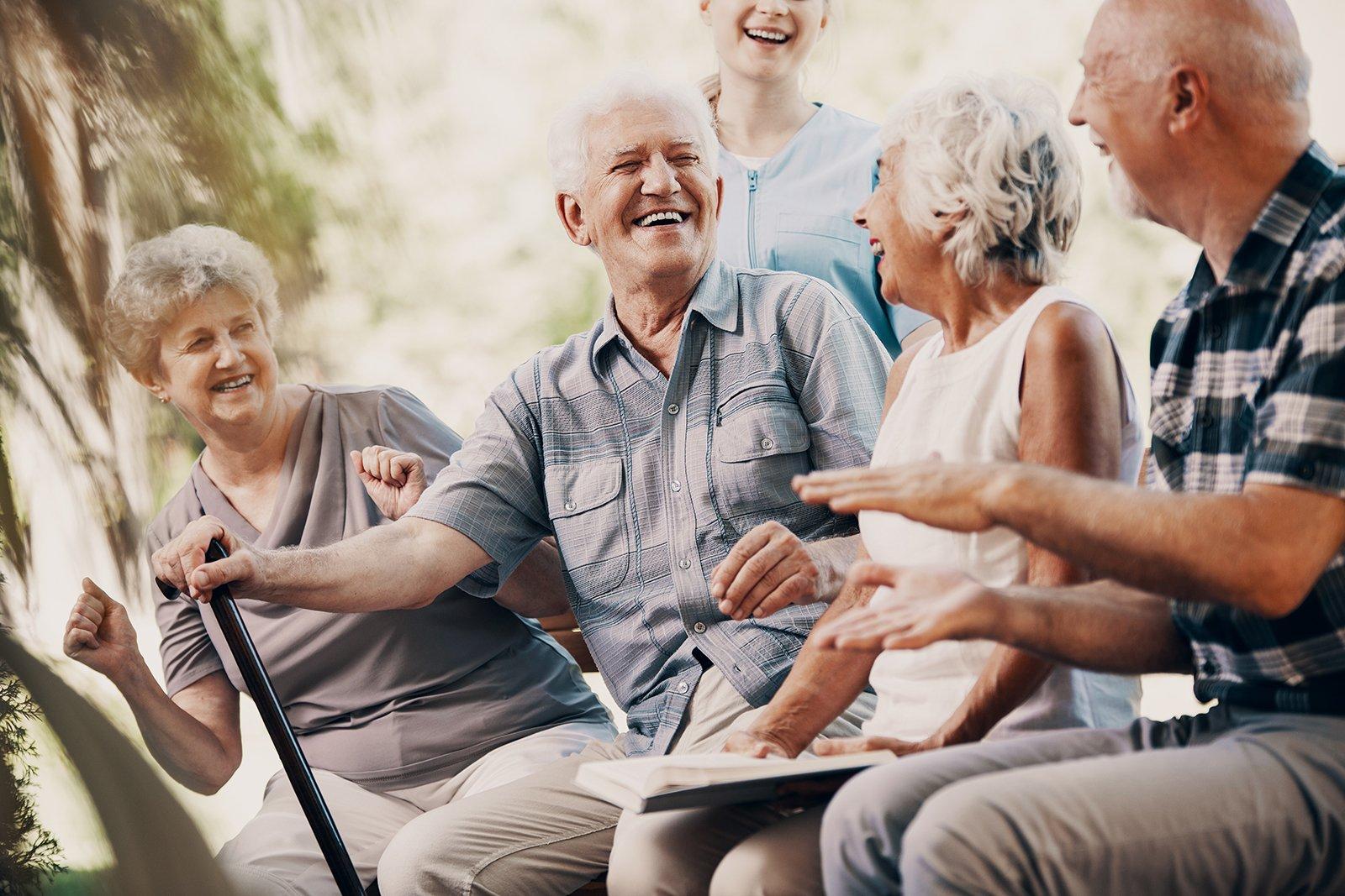 Mehrere Senioren sitzen im Park auf einer Bank in Deggendorf