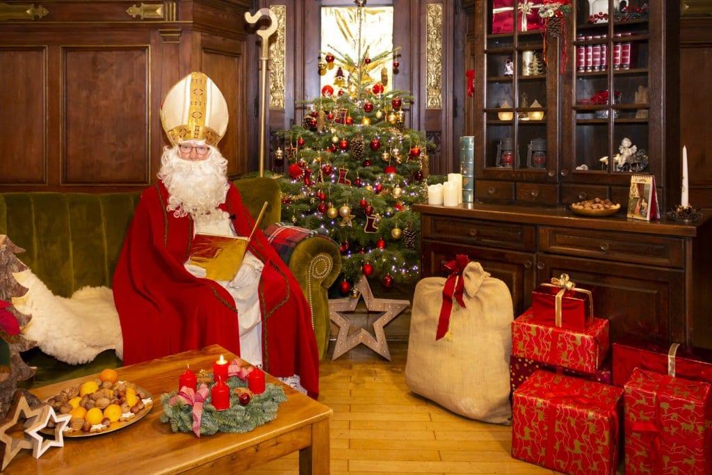 """Nikolaus in """"seinem Wohnzimmer"""" sitzend auf einer grünen Couch neben Päckchen und Christbaum"""