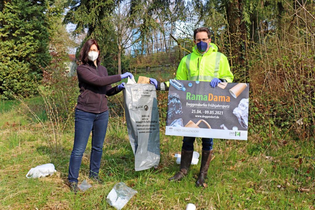 Die Umweltbeauftragte der Stadt Deggendorf mit dem Oberbürgermeister beim Aufräumen von Müll auf einer Wiese