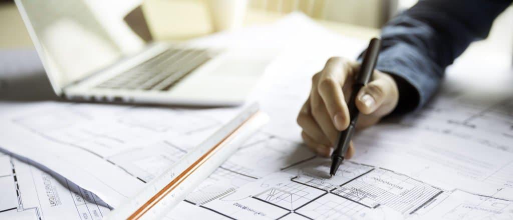 Jemand zeichnet mit Stift auf einen Bauplan.
