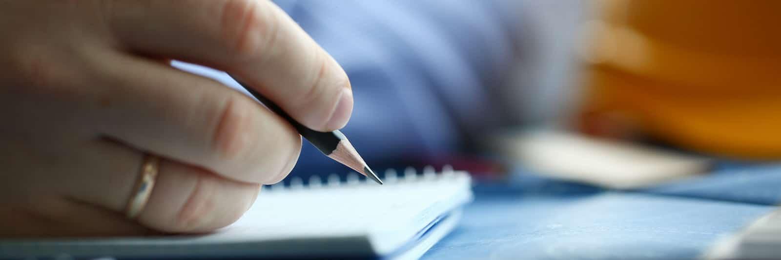 Jemand schreibt mit einem Bleistift auf einen Block Papier