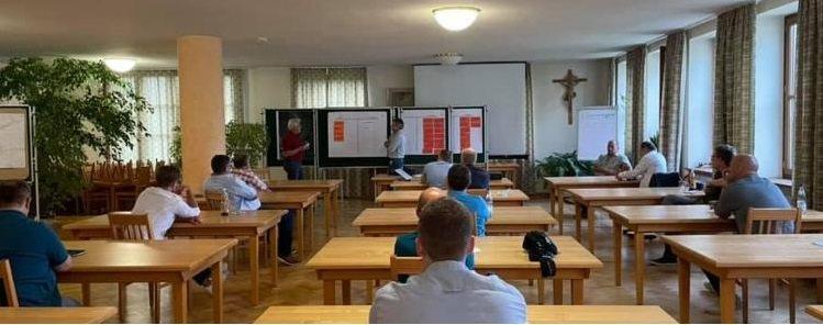 "Blick in den Workshop ""Dorferneuerung Mietraching"", wo Personen aufmerksam den Vorträgen an der Tafel folgen"