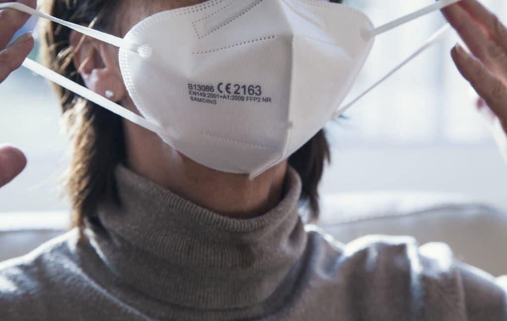 Eine Frau mit grauen Pulli und mittellangen braunen Haar zieht sich eine FFP2-Mund-/ Nasenmaske auf.