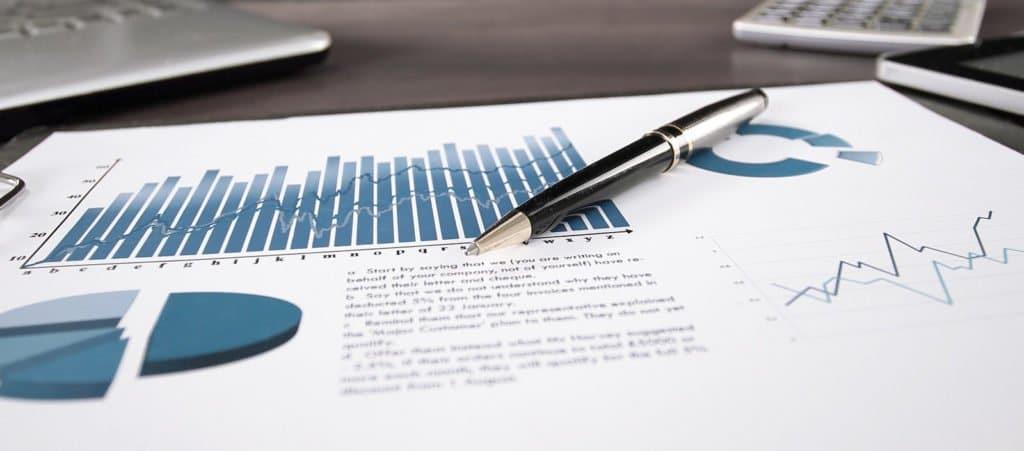 Papier mit Zahlen, Diagrammen und einem Stift