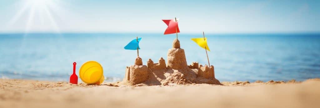 Sandburg am Strand als symbolisches Foto für Ferien