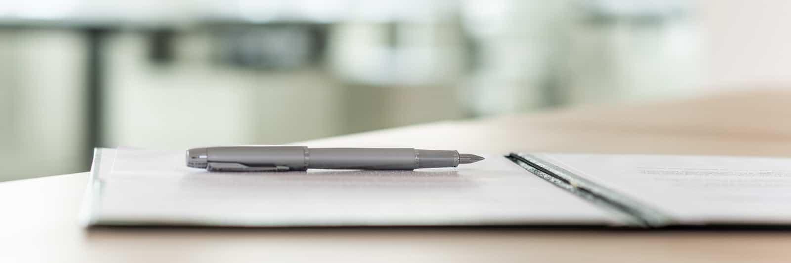 Auf einem Schreibtische liegt ein Dokument und ein Stift