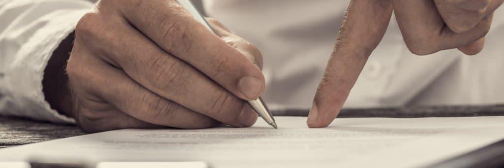 Jemand zeigt auf ein Blatt Papier und bittet den Antragsteller zu unterschreiben