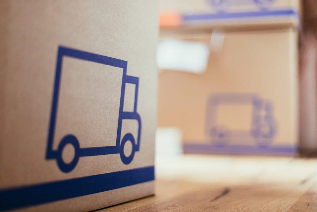 Braune Umzugskartons mit einen Lieferwagen bedruckt in einer frisch bezogenen Wohnung auf dem Holzboden