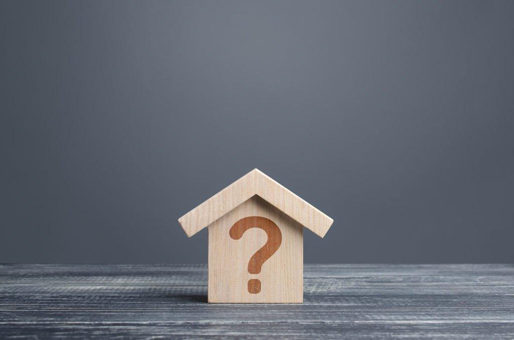 Kleines Holzhaus mit einem Fragezeichen versehen auf einer grauen Tischplatte
