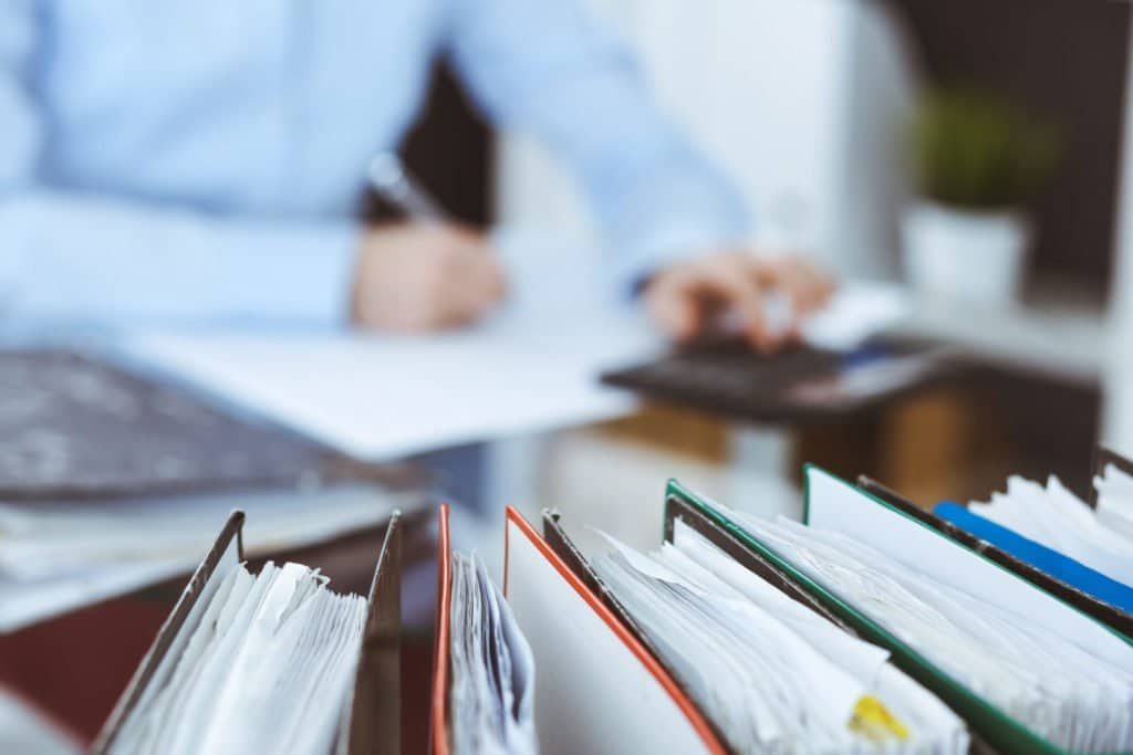 Mann unterschreibt ein Dokument hinter mehreren Ordnern