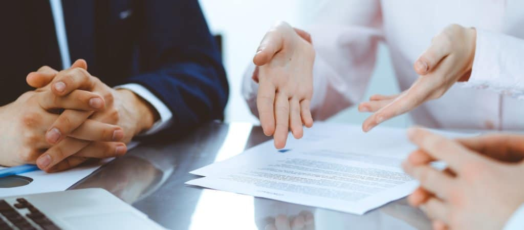 Mehrere Personen sitzen an einem Tisch mit Vertragsunterlagen und Laptop und besprechen rechtliche Dinge.
