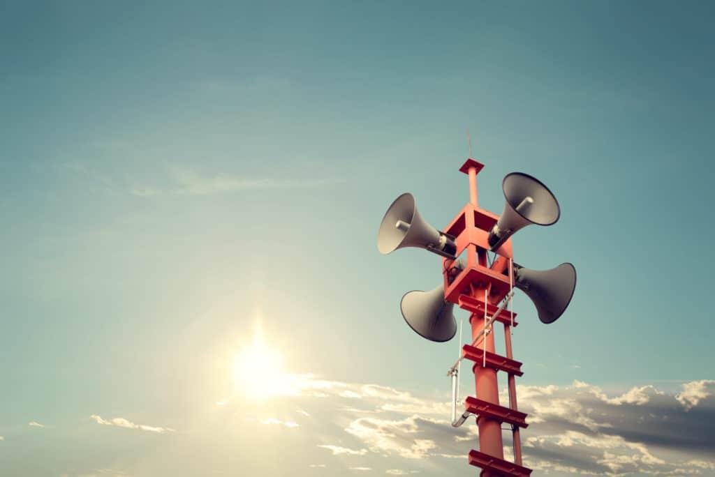 Vier Sirenen-Lautsprecher an einem roten Metall-Mast zur Alarmierung der Bürger in Not-Situationen