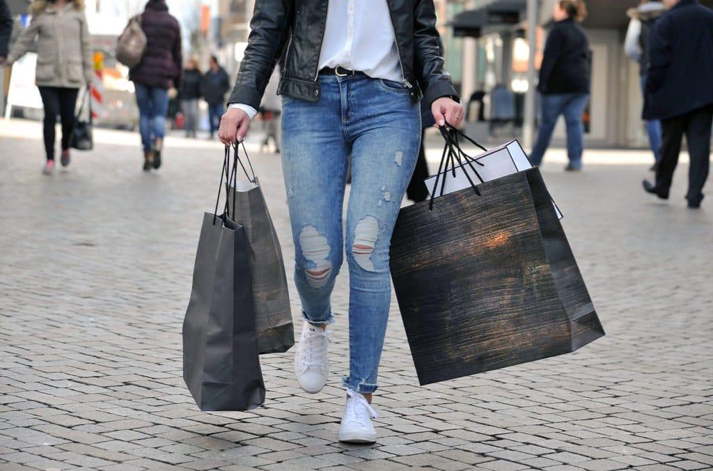 Frau schlendert mit prallen Einkaufstüten durch die Fußgängerzone
